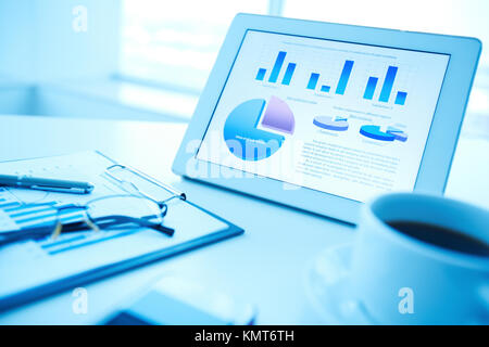 Image of an office workplace with document, touchpad and a cup of coffee - Stock Image