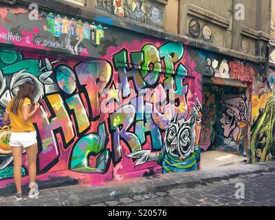 Tourist in Hosier Lane Melbourne with street art on walls - Stock Image