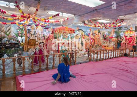 An anonymous Hindu devotee sits alone in silent prayer & meditations near the altar at the Dayaram Mandir in Jamaoc, Queens, New York - Stock Image