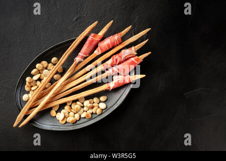 Prosciutto-wrapped Italian grissini with roasted almonds, shot from above on a black background with a place for text - Stock Image