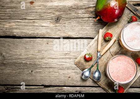 Fresh berry smoothie. On a wooden background. - Stock Image