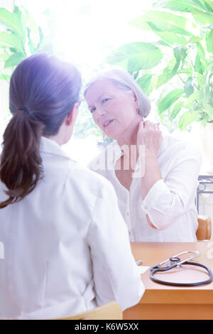 Senior female patient consulting her general practitioner or doctor on account of acute neck pain caused by muscular tension, copy space - Stock Image
