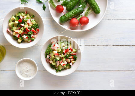 Tasty healthy vegetable salad from avocado, radish, cucumber, greens in bowl over light wooden background with copy space. Organic natural or vegetari - Stock Image