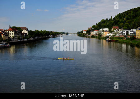 Three men row their boat on the River Neckar on a beautiful summer day. Heidelberg, Germany. - Stock Image