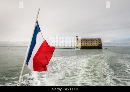 the flag of france with a sea fortress of Napoleon in the background - Stock Image