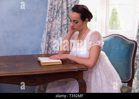 Pretty young woman in authentic regency dress reading a book in vintage room - Stock Image