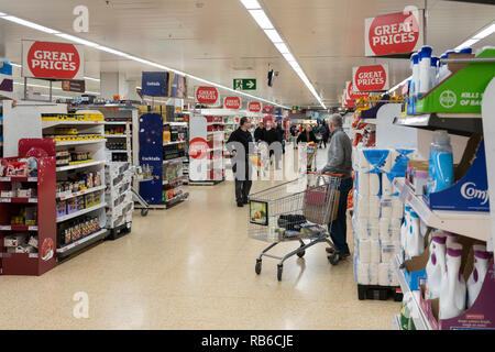 Shoppers in the central aisle in a large Sainsbury's supermarket in the UK - Stock Image