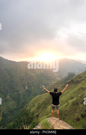 Man standing with raised hands on the top of Small Adams peak. Ella, Sri Lanka - Stock Image