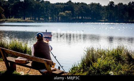 Pen Pond's pond life is captured by a seated artist in London's famous Richmond Park - Stock Image