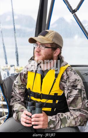 Tourist On Boat With Binoculars, Seward, Southcentral Alaska, USA - Stock Image