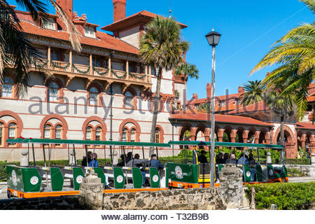 A tour trolley passes Flagler College, formerly the Ponce de Leon Hotel, in the historic district of Saint Augustine, Florida USA - Stock Image