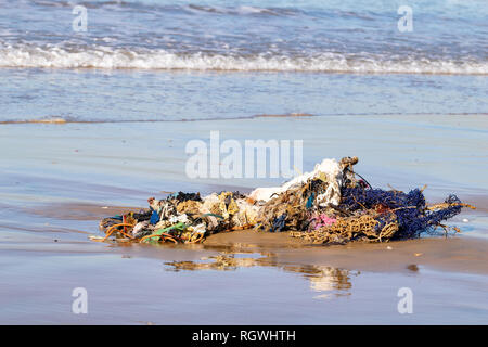 Rubbish, clothing and household belongings washed up from the Atlantic Ocean on Agadir beach, Morocco, Africa - Stock Image