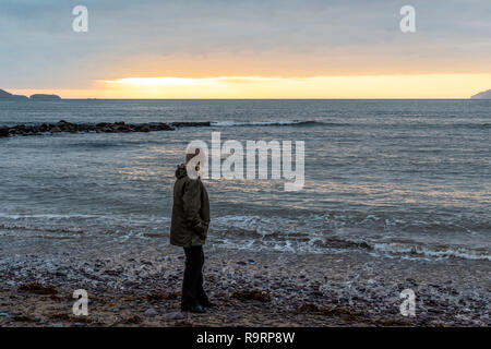 Woman alone on Waterville Beach, County Kerry Ireland at sunset - Stock Image