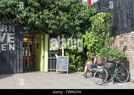 Lady sitting on bench with bicycle next to her outside Dalston Eastern Curve Garden, London Borough of Hackney. - Stock Image