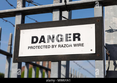 A warning sign stating Danger Protected by Razor Wire mounted on railings outside a business in Warrington May 2018 - Stock Image