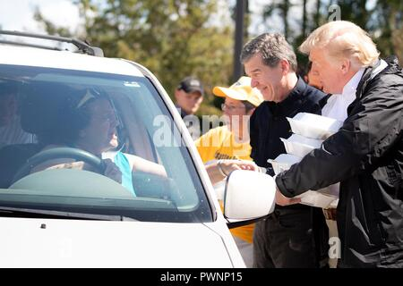 U.S President Donald Trump, right, and North Carolina Governor Roy Cooper assists in handing out meals to victims of Hurricane Florence at the Temple Baptist Church September 19, 2018 in New Bern, North Carolina. Florence dumped record amounts of rainfall along the North & South Carolina coast causing widespread flooding. - Stock Image