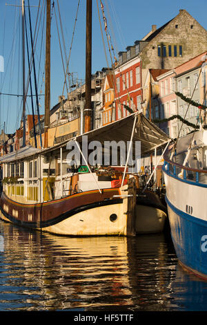 Denmark, Copenhagen, Nyhavn, boats moored beside quayside warehouses converted to housing and restaurants from canal - Stock Image