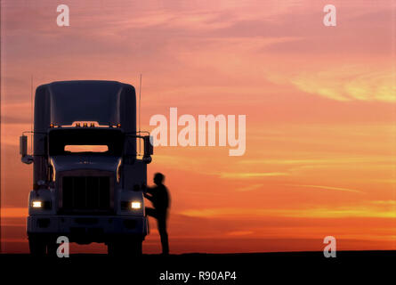 A silhouette of a truck driver getting into the cab of his commercial Class 8 truck tractor at sunrise. - Stock Image