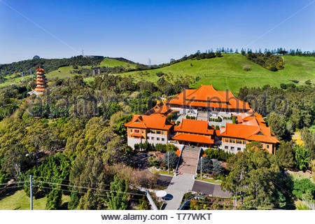 Chinese garden around Nan Tien Buddhist temple and high-rise pagoda tower on green hills near Wollongong in NSW, Australia. Elevated aerial view over  - Stock Image