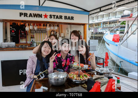 A group of Oriental visitors eating seafood on board the Prawn Star, Cairns, Far North Queensland, FNQ, QLD, Australia - Stock Image