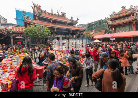 Smoke spreads around Longshan Temple in Taipei on Lunar New Year's Day as visitors burn incense and pray to mark the arrival of the Year of the pig. - Stock Image