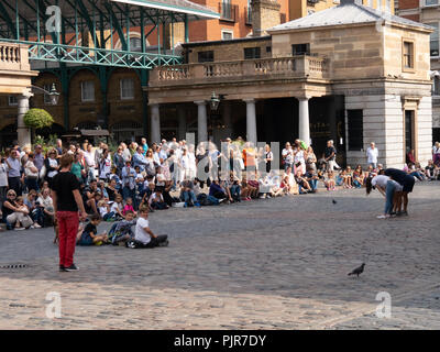Crowds of people watch a street performance in covent Garden, London, England - Stock Image