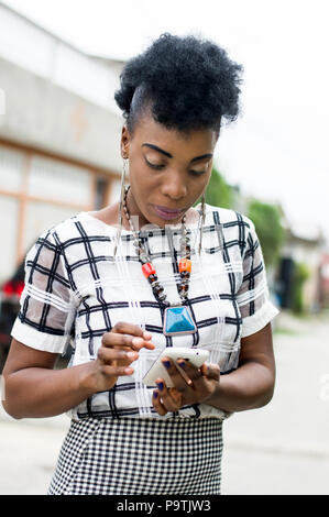 Portrait of African woman focused on her mobile phone. - Stock Image