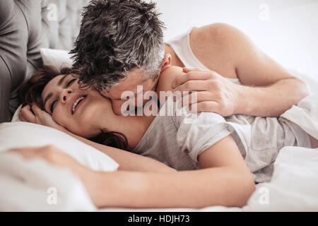Man kissing his girlfriend on her neck while she is smiling and enjoying. Early morning bedroom scene. - Stock Image