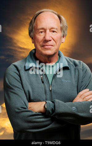 Portrait of confident middle aged man against sunset clouds background - Stock Image