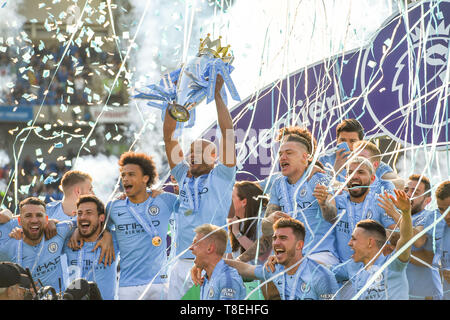 Vincent Kompany of Manchester City lifts the Premier League trophy after the Premier League match between Brighton & Hove Albion and Manchester City  at the American Express Community Stadium 12 May 2019 Editorial use only. No merchandising. For Football images FA and Premier League restrictions apply inc. no internet/mobile usage without FAPL license - for details contact Football Dataco - Stock Image