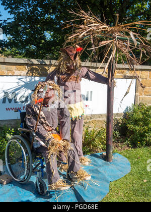 Marske North Yorkshire August 25th/ Like many Yorkshire villages Marske by the Sea has a weeklong Scarecrow Festival which started today 25th August,  many different organisations and social groups have made scarecrows an erected them around the village.  Parents and children can get a trail map to follow and view all the exhibits.  There is a prize draw at the end of the week. Display by the Leonard Cheshire home for the disabled, a man on a destert island with a partner in a wheelchair' Credit: Peter Jordan_NE/Alamy Live News - Stock Image
