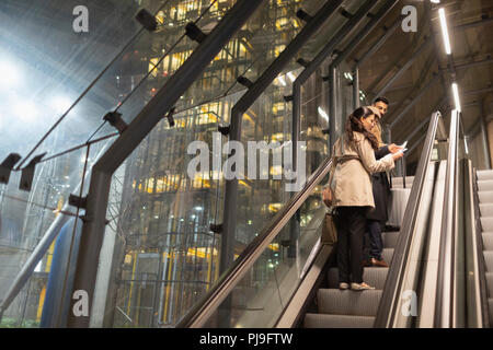 Business people with suitcase talking on urban escalator at night - Stock Image