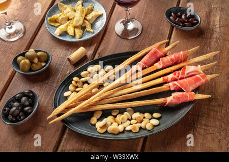 Italian antipasti. Grissini breadsticks with prosciutto di parma and roasted almonds, with olives and artichokes, with wine glasses - Stock Image