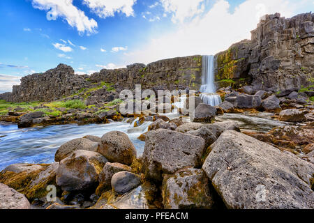THINGVELLIR NATIONAL PARK, ICELAND.  3RD AUG 2016: Long exposure of Oxararfoss waterfall with rocky pool in the foreground and blue sky with some clou - Stock Image