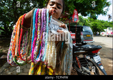 A young girl sells beads and necklaces to tourists in Chennai, India - Stock Image