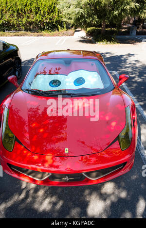 Red  Ferrari 458 Italia with funny Lightning McQueen Eyes, Cars movie merchandising windshield sun shades. In Silicon - Stock Image