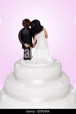 A cake topper showing the groom crossing his fingers - Stock Image