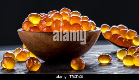 Red caviar in the bowl on wooden background. Macro picture. - Stock Image