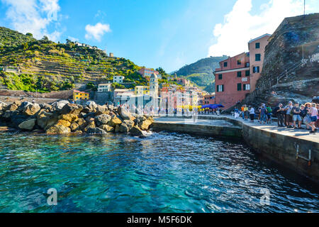 Tourists enjoy the sea and town on a sunny summer morning at the hillside village of Vernazza Italy, part of the - Stock Image