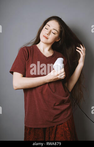 young brunette woman blow-drying her long hair with blow dryer or drier at home - Stock Image