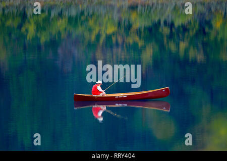 A senior man wearing a red vest fishing from a  red canoe on a tranquil lake. - Stock Image