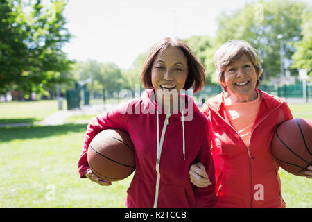 Portrait happy, active senior women friends playing basketball in sunny park - Stock Image