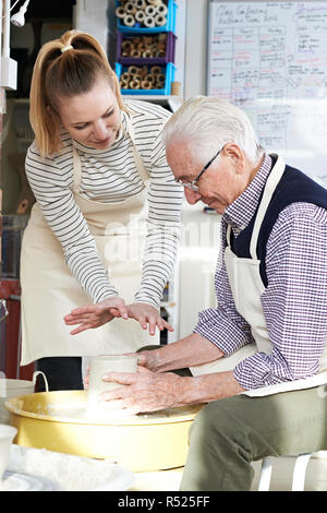 Senior Man With Teacher In Pottery Class - Stock Image