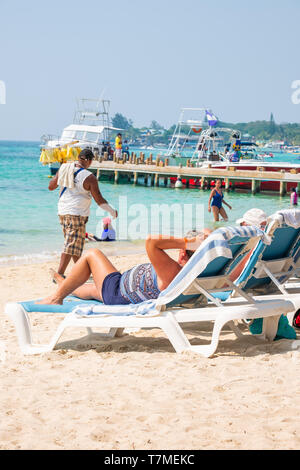 Tourist relaxes in the sun at west bay beach Roatan Honduras on a lounge chair. - Stock Image
