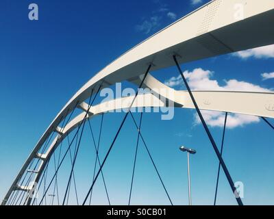 Top portion of a small white modern bridge, with blue sky. - Stock Image
