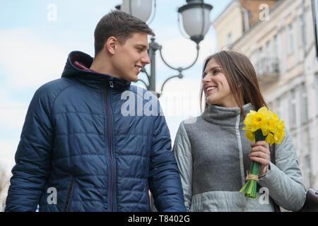 Couple in love in city. Young happy man and woman in spring city talking, walking, with bouquet of yellow flowers daffodils. - Stock Image