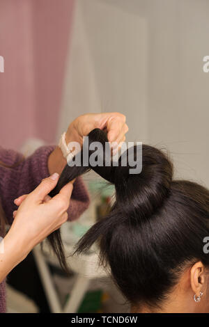 Hair stylist hands form high tuft of hair. Learning to create an evening hairstyle. Hairdressing workshop. Beauty industry. Space for text - Stock Image