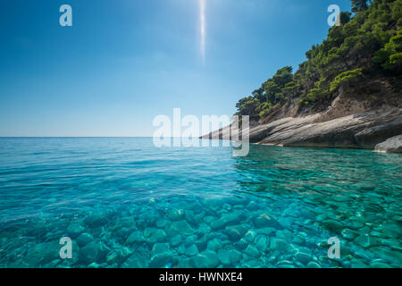 Clear blue sea off a rocky coastline. - Stock Image