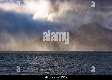 Rays of sunshine illuminate a rain shower over Gullesfjorden on island Hinnøya in  northern Norway. - Stock Image
