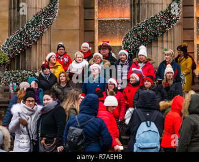 Edinburgh, Scotland, United Kingdom, 8th November 2018. Christmas celebrations: A busy Saturday in the capital city centre. Christmas carol singers outside The Dome on George Street raising money for Edinburgh Children's Hospital with people walking past stopping to watch - Stock Image